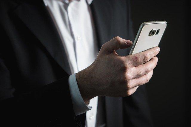 osoba držící mobilní telefon