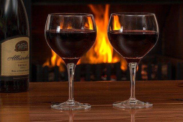 skleničky vína s hořícím krbem